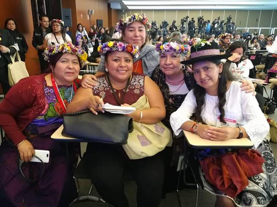 Un grupo de personas sentadas sonriendo  Descripción generada automáticamente